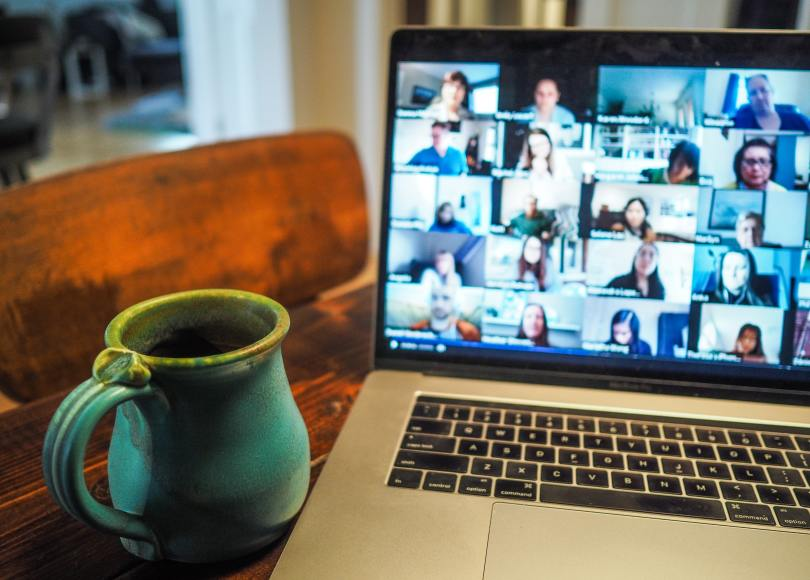 Open laptop with approximately 20 people tiled on the screen in an online meeting. A mug is on the table to the left of the laptop.