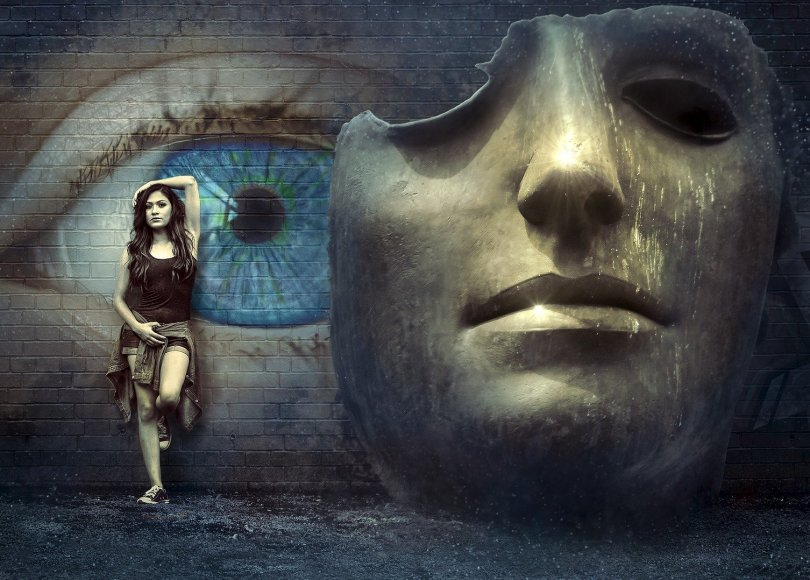 Description: Fantasy image. Large Surreal Mask in front of a blue eye painted on a wall. I girl is leaning on the wall to the left of the mask.